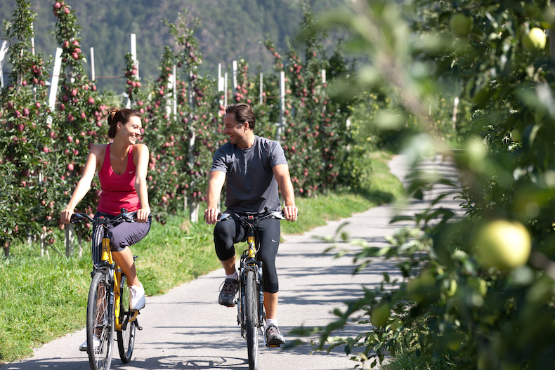 Couples cycling around the orchards at Priedlhof Hotel, Naturns, South Tyrol, Italy