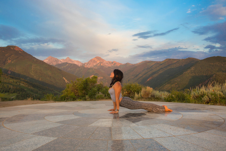 Lady doing yoga pose, upward facing dog in Snowmass with mountain backdrop